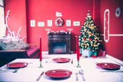 Tabla maravillosamente puesta del Año Nuevo con las placas y los cubiertos rojos en un fondo del sitio adornado con el árbol de n Fotos de archivo