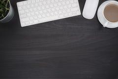 Tabla negra del escritorio de oficina con el ordenador y la taza del coffe imagen de archivo