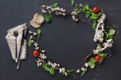 Tabla negra del restaurante adornada con las flores y la ensalada Fotos de archivo