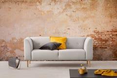 Tabla negra y sofá gris con los amortiguadores en la sala de estar simple interior con la pared de ladrillo roja Foto verdadera foto de archivo