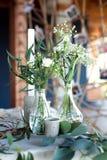Tabla para las huéspedes, cubierta con un mantel, adornada con las velas, floreros de cristal transparentes, flores frescas y ser imágenes de archivo libres de regalías