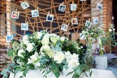 Tabla para las huéspedes, cubierta con un mantel, adornada con las velas, floreros de cristal transparentes, flores frescas y ser foto de archivo