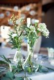 Tabla para las huéspedes, cubierta con un mantel, adornada con las velas, floreros de cristal transparentes, flores frescas y ser imagenes de archivo