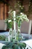 Tabla para las huéspedes, cubierta con un mantel, adornada con las velas, floreros de cristal transparentes, flores frescas y ser fotografía de archivo