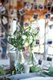 Tabla para las huéspedes, cubierta con un mantel, adornada con las velas, floreros de cristal transparentes, flores frescas y ser imagen de archivo libre de regalías