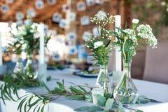 Tabla para las huéspedes, cubierta con un mantel, adornada con las velas, floreros de cristal transparentes, flores frescas y ser imagen de archivo