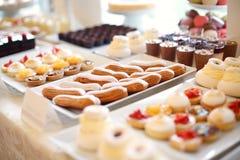 tabla por completo con las mini tortas y dulces Fotos de archivo libres de regalías