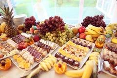 Tabla por completo de frutas y de pequeñas tortas Imagenes de archivo