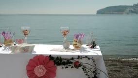 Tabla por el mar con los bocados dulces de las cosas, bebidas para el banquete en el aire fresco almacen de video