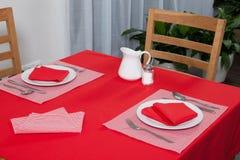 Tabla puesta - la bifurcación y la cuchara pusieron en el paño rojo y la placa blanca Imagenes de archivo