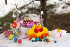 Tabla puesta para Pascua: pollo del juguete con los huevos de Pascua coloridos Foto de archivo