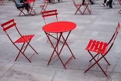 Tabla roja y sillas al aire libre Imágenes de archivo libres de regalías