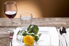 Tabla Romantically puesta con las rosas amarillas y el vino, atmósfera romántica Imagen de archivo