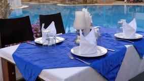 Tabla servida cerca de la piscina con agua azul en el centro turístico de Egipto almacen de video