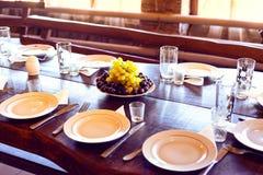 Tabla servida en el restaurante, placas, bifurcaciones, cuchillos, vidrios en el centro de las uvas maduras fotos de archivo