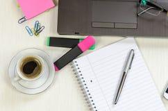 Tabla sucia de la oficina con el cuaderno, la libreta y el café Imágenes de archivo libres de regalías