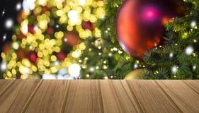 Tabla superior de madera con el árbol de navidad adornado con la bola roja con foto de archivo