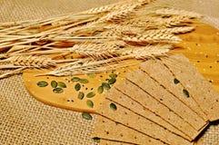 Tabla superior de rebanadas de pan sano del cereal con la decoración del trigo en fondo de madera de la tabla fotos de archivo libres de regalías