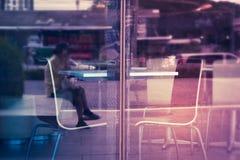 Tabla vacía con las sillas en una tienda al lado de la ventana de cristal Imágenes de archivo libres de regalías