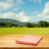 Tabla vacía cubierta con el mantel comprobado sobre paisaje hermoso Foto de archivo libre de regalías