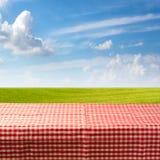 Tabla vacía cubierta con el mantel comprobado sobre prado verde y el cielo azul Foto de archivo libre de regalías