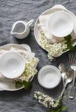 Tabla vacía de la porción romántica con la loza blanca, flores, servilletas en el fondo gris, visión superior Tabla casera acoged fotos de archivo