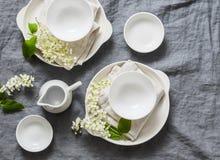 Tabla vacía de la porción romántica con la loza blanca, flores, servilletas en el fondo gris, visión superior Tabla casera acoged imagenes de archivo