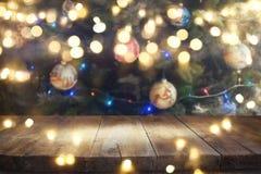 Tabla vacía delante del árbol de navidad con el fondo de las decoraciones para el montaje de la exhibición del producto Foto de archivo