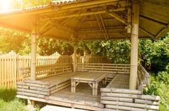 Tabla y asientos de bambú debajo de un toldo de bambú con los haces soleados foto de archivo libre de regalías
