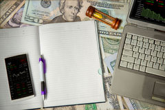 tabla y pluma móviles del precio del mercado libre en aislante del cuaderno en los billetes de dólar fondo, tabla del precio del  foto de archivo libre de regalías