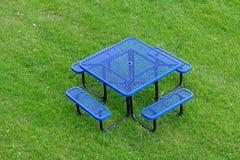 Tabla y silla azules en prado imagenes de archivo