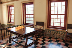 Tabla y silla rústicas en un cuarto iluminado por el sol  Foto de archivo libre de regalías