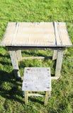 Tabla y silla viejas en un fondo de la hierba verde en un día de verano soleado imagen de archivo