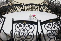Tabla y sillas blancas en el café con las flores Fotos de archivo libres de regalías