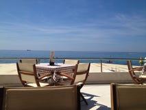 Tabla y sillas con la opinión del mar fotos de archivo