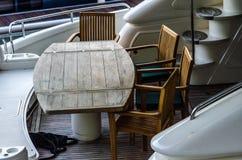 Tabla y sillas de madera en la popa de una nave grande anclada adentro Foto de archivo libre de regalías
