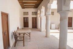 Tabla y sillas de madera en la yarda diseñada árabe soleada con las columnas Imagen de archivo libre de regalías
