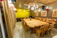 Tabla y sillas de madera grandes hechas a mano en el piso de mármol Imagen de archivo libre de regalías
