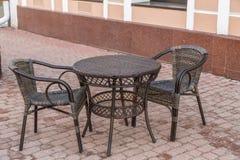 Tabla y sillas de mimbre en café vacío en la calle en la ciudad Imagenes de archivo