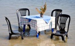 Tabla y sillas en el mar Imagen de archivo libre de regalías