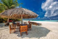 Tabla y sillas en la playa en la isla tropical, Maldivas fotografía de archivo