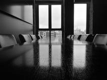 Tabla y sillas en un cuarto con una ventana y una vista de la ciudad imagenes de archivo