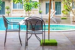 Tabla y sillas modernas en cubiertas de madera en el lado de la piscina imágenes de archivo libres de regalías