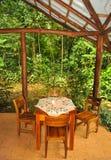 Tabla y sillas para cuatro en un ajuste de la selva tropical Foto de archivo libre de regalías
