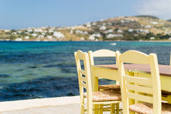 Tabla y sillas por el mar Imagen de archivo libre de regalías