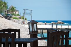 Tabla y sillas vacías en un restaurante tropical de la playa imagen de archivo