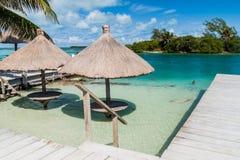 Tabla y un parasol en un agua en la isla del calafate de Caye, Beli imagen de archivo
