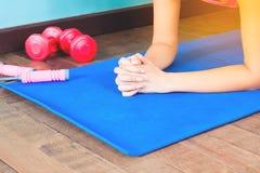 Tablaje de la mujer de la aptitud en la estera de la yoga, resolviéndose en casa, la aptitud y la forma de vida sana Foto de archivo libre de regalías