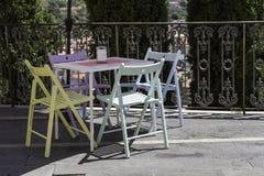 Tablas coloreadas y sillas del vintage por un café Imagen de archivo libre de regalías