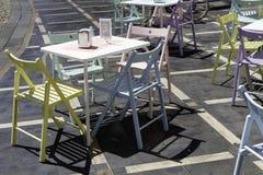 Tablas coloreadas y sillas del vintage por un café Fotos de archivo libres de regalías